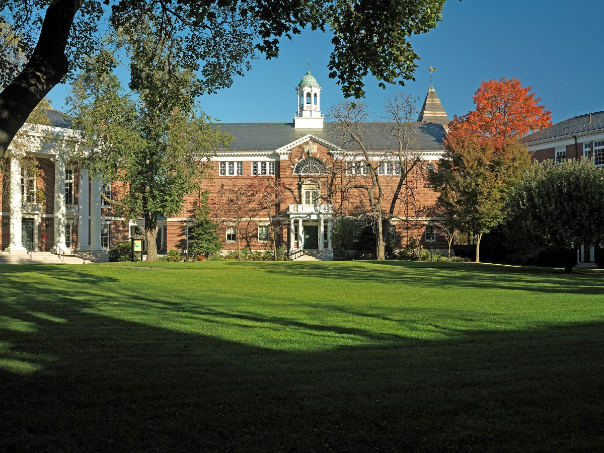 Historical brick building with cupola and columns at the entrance with a green lawn in front