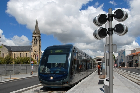 Passengers boarding tram with cathedral in background
