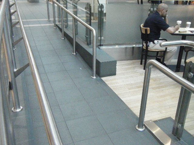 Ramp with railings on either side and opening to seating area