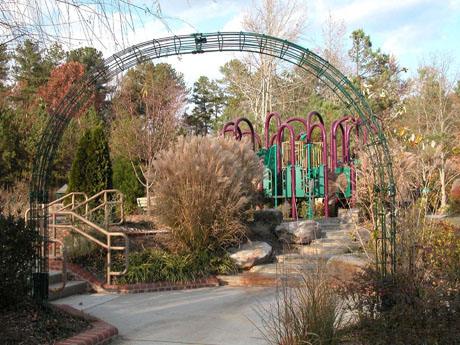 Green archway in front of park with shrubbery and play structure visible