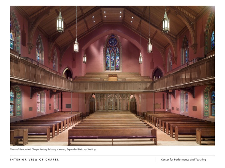 Interior view of the chapel from the altar with pink walls, rows of pews as well as balcony seating