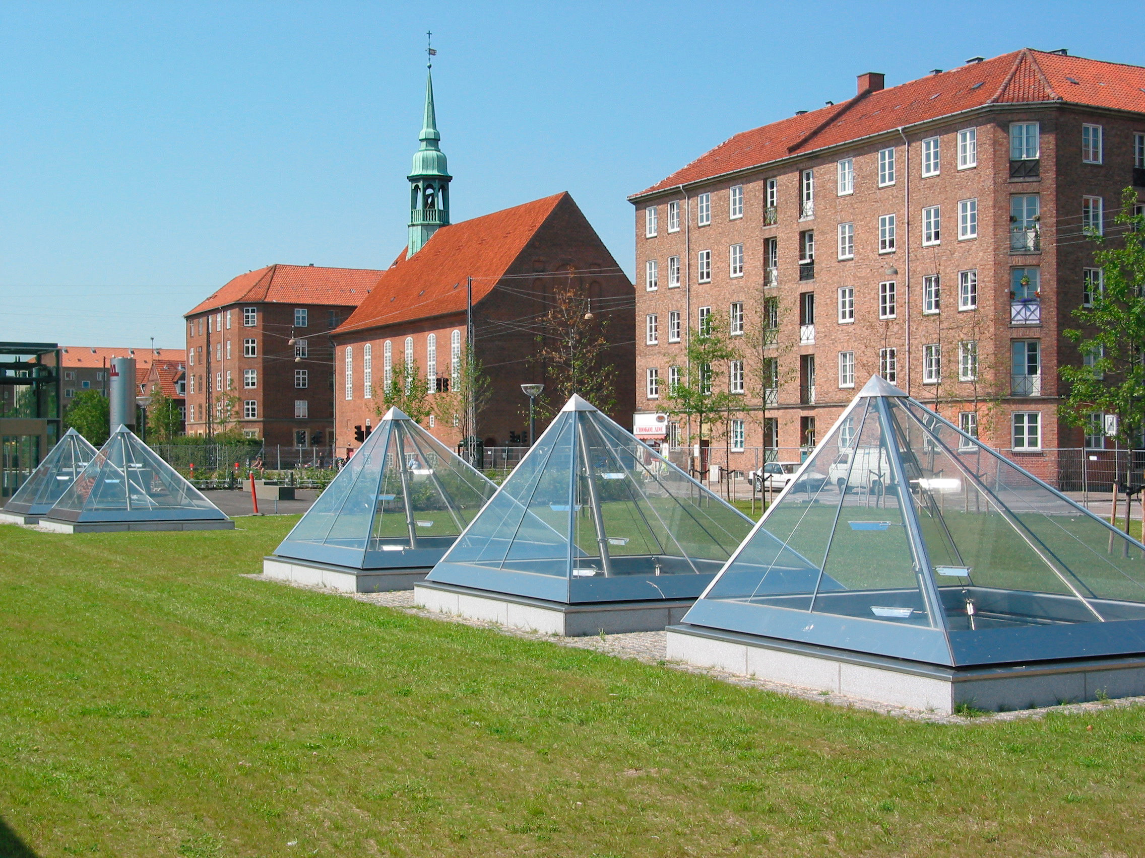 Glass prism pyramids in a grass lawn in front of historic brick buildings