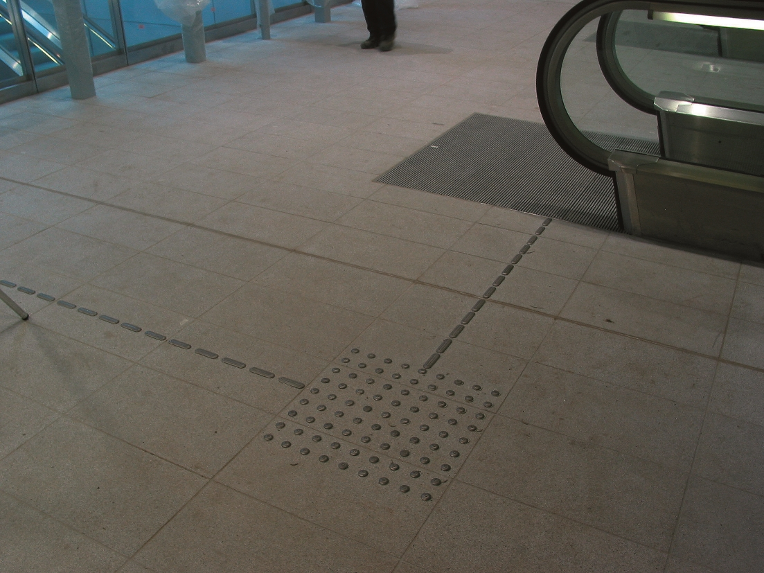 Dark tile floor with metal trncated domes in a square pattern