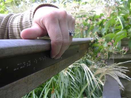 Hand reading the braille on outside of handrail
