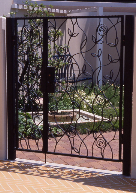 Black iron gates with stylized flowers in front of garden