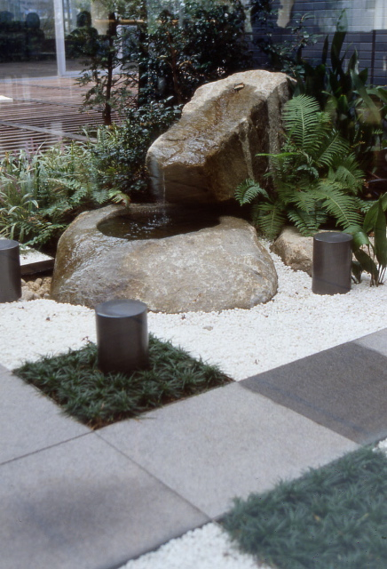 Meditation garden with a water feature, large rocks, and gravel base