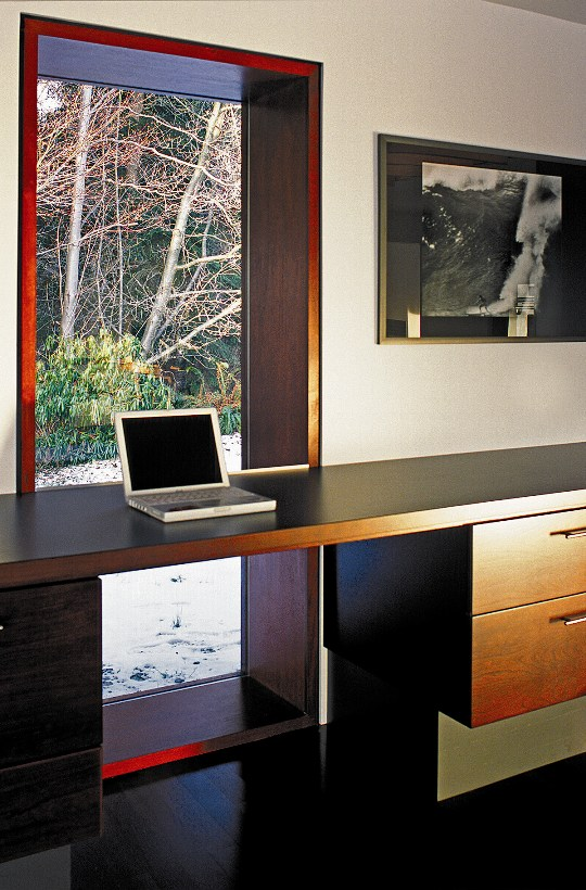 A large, deep, single pane window with a simple wooden desk table surface in front with a laptop on it.