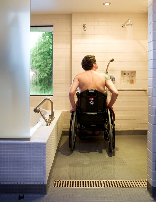 Siple in his wheelchair in the shower, shower has white wall tiles and light green floor tiles