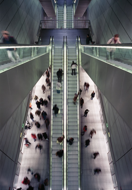Passengers using escalators in a metro station