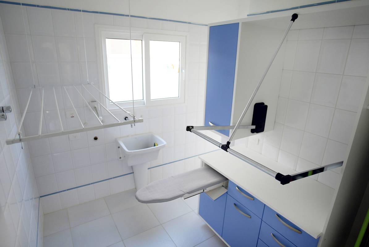 White laundry room with small sink on far wall and ironing board sticking out from cabinets on the right