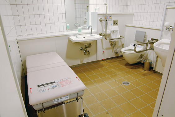 Large single user bathroom with brown tiled floor and white fixtures.