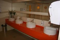 Bright orange counter with four white sinks