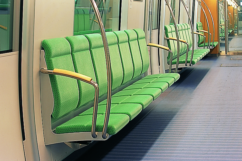 Close up of high backed seating on the subway car and curved stainless steel handgrips.