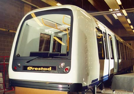 New white train car with large windows and bright yellow handrails inside.