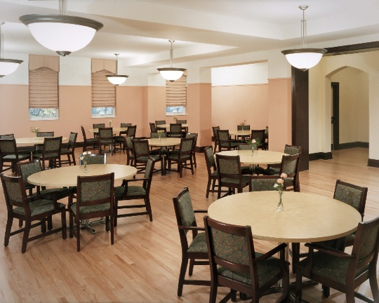Several round tables surrounded by five chairs each in typical dining hall layout