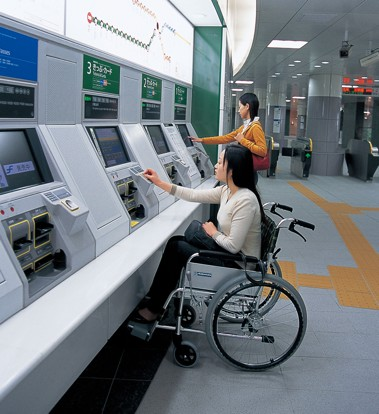 Two women, one in a wheelchair and one standing, using fare vending machines.