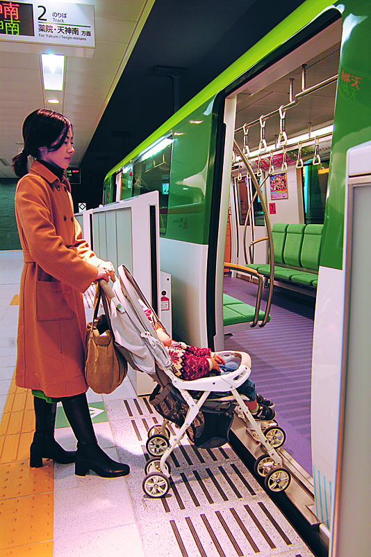 Photo of woman pushing a baby carriage across the minimal gap between the platform and train.