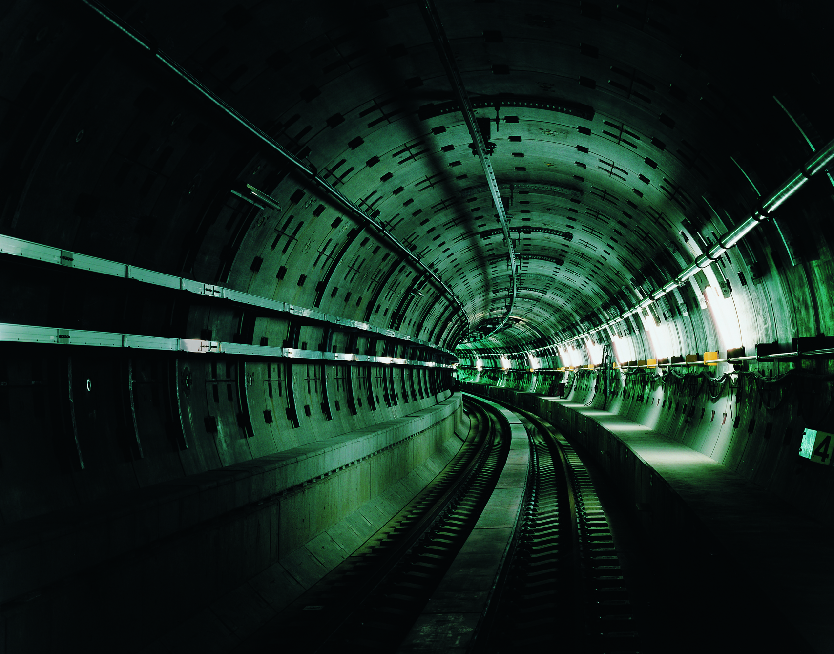View looking down a curved subway tunnel, mostly darkish and dark