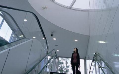 A woman at the top of the stairwell looks up at a semi-circle skylight