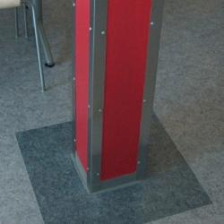 Bright red column with metal corners on top of a tile of different color from the rest of the floor