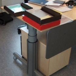 Desk with adjustable length leg and small filing cabinet stowed beneath it