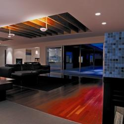 Diagonal view of both living room and kitchen shows hardwood floor as sliding glass doors to outside
