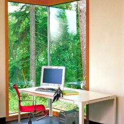 90 degree angle glass wall with simple wooden desk in front of it.