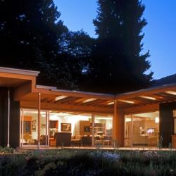 Nighttime shot of the house shows bright lights shining through the large windows of the kitchen and living room