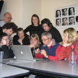 Group of users with various abilities gathered around laptop testing equipment