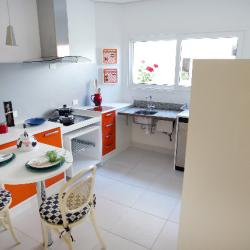 White kitchen with bright orange and red cabinet drawers and small breakfast table
