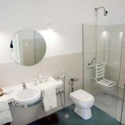 Bright bathroom with light brown tile about halfway up the walls, a glass shower with a transfer seat