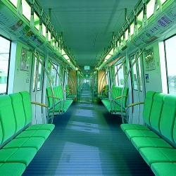 Interior of subway car with green seats along the wall and three doorways per side of car.