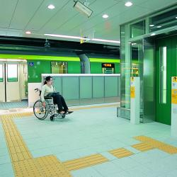 Woman in wheelchair exits train onto brightly lit platform and heads to a large glass elevator.