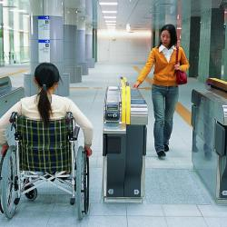 A woman in a wheelchair rolls through a wide fare gate as a woman walks through in the other direction