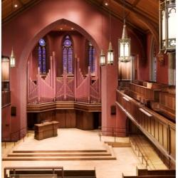 Chapel with dark pink walls and ornate organ behind the altar