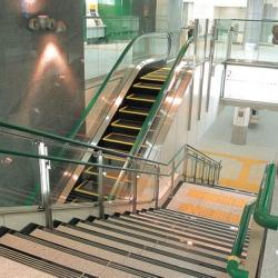 Stairs and escalator crossing in a lobby. There are tactile bumps on the surface of the stair landings.