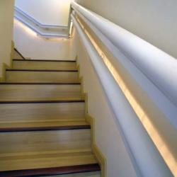 Stair with contrasting wood at the edge of each tread and two handrails on one side at different heights.
